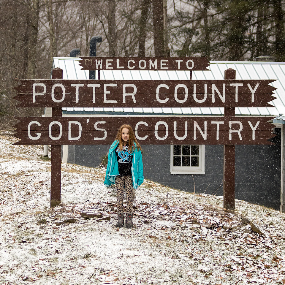 Hailee standing next to the God's Country sign in Potter County, PA.