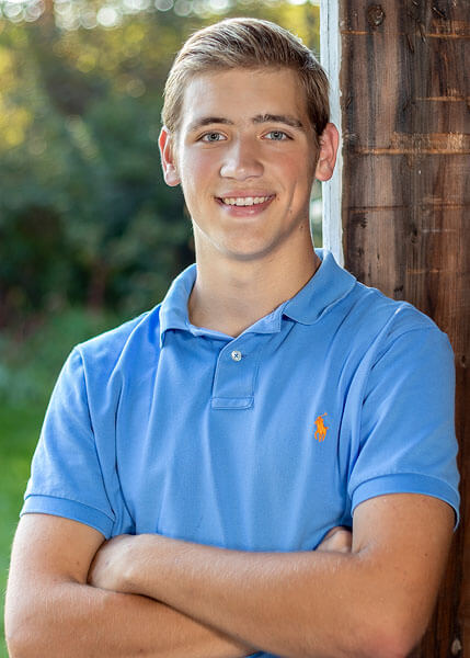 An old barn door serves as the setting for this senior portrait by State College portrait photographer Rusty Glessner